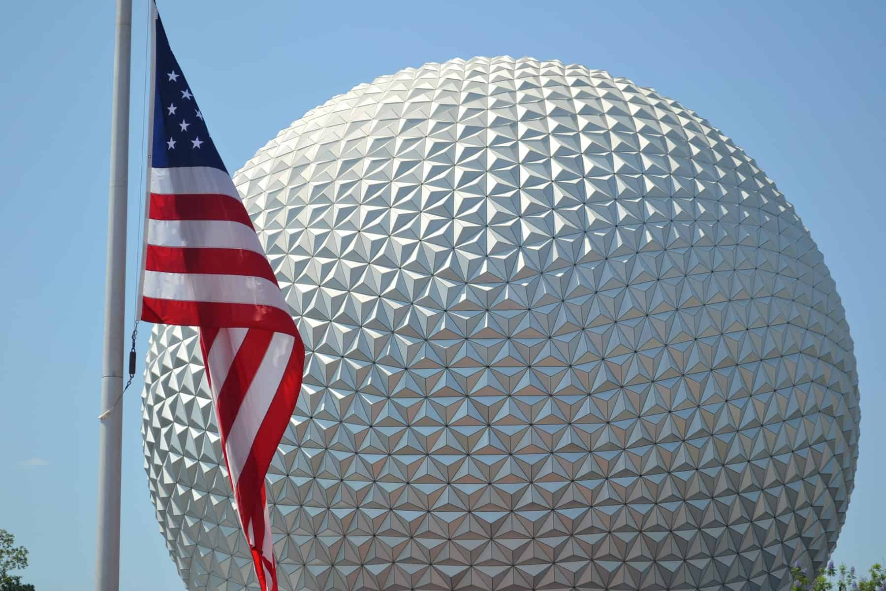 american flag in front of spaceship earth